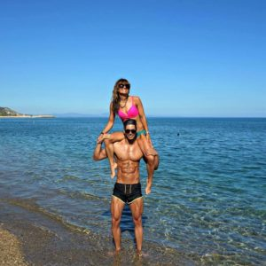 Lucas Liaskos at the beach with his girlfriend on his shoulders