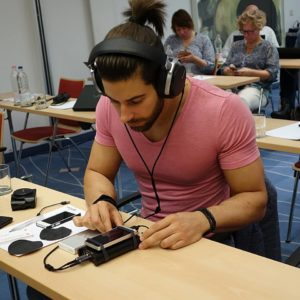 Lucas Liaskos tinkering with his gadgets while working